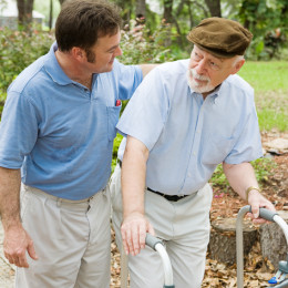 Adult son out for a walk with his father, who has alzheimers disease.